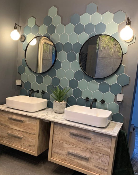blue and green tiles bathroom with double sinks and fender wall lights