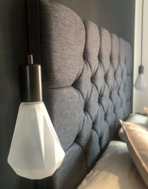 Keren christalle light draped over a grey headboard in a grey and white bedroom