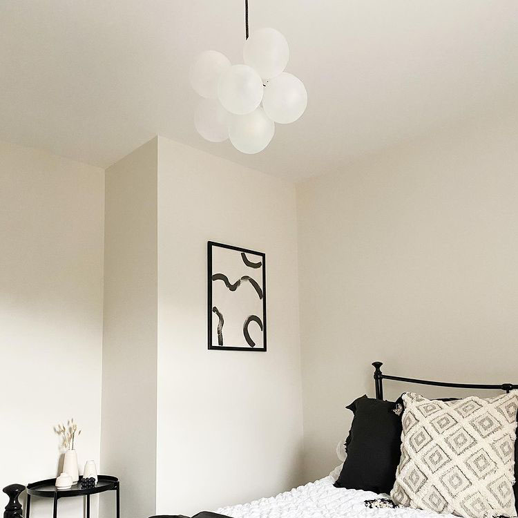 small frosted bubble chandelier in an all white bedroom