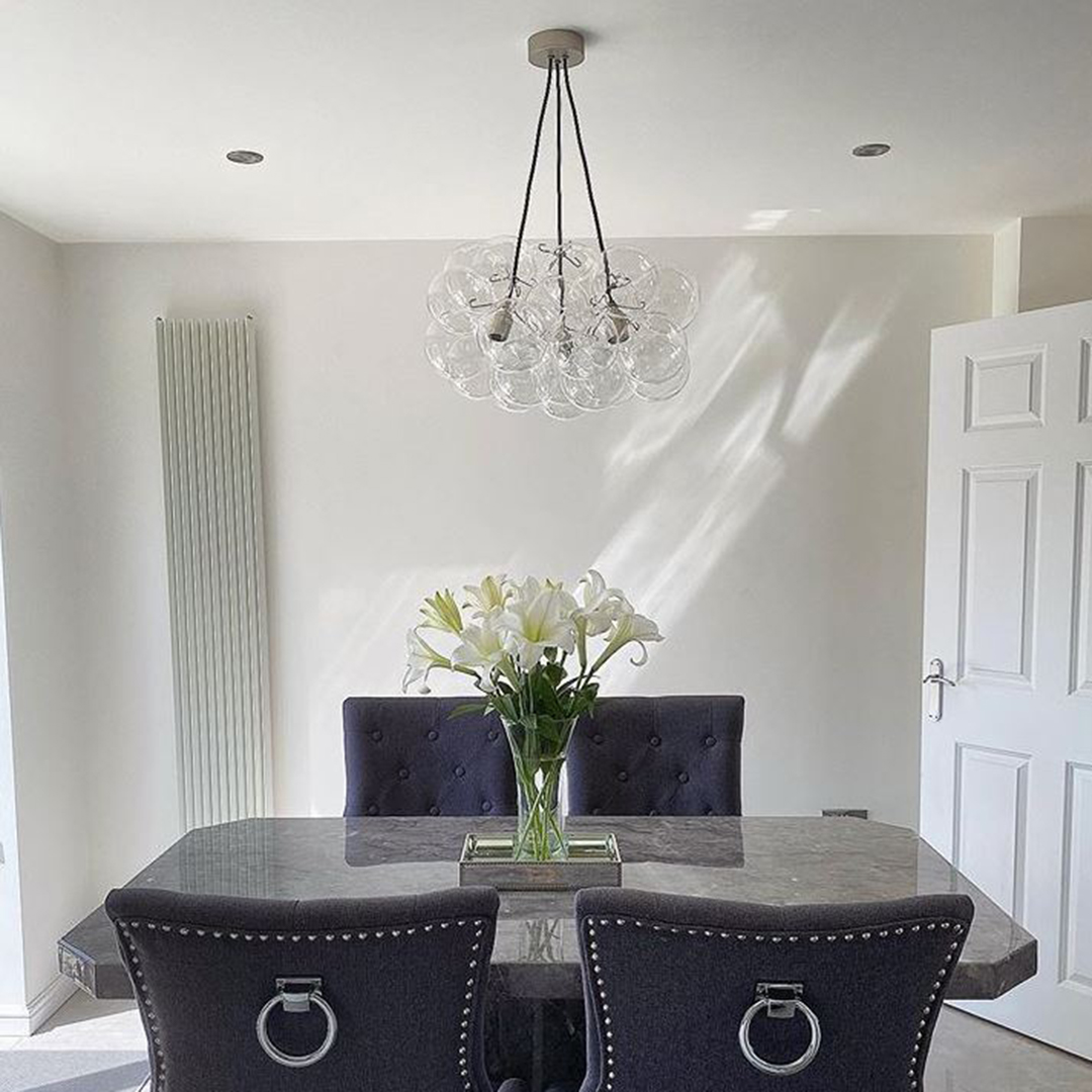 medium bubble chandelier suspended above a black marble dining table in a white dining room