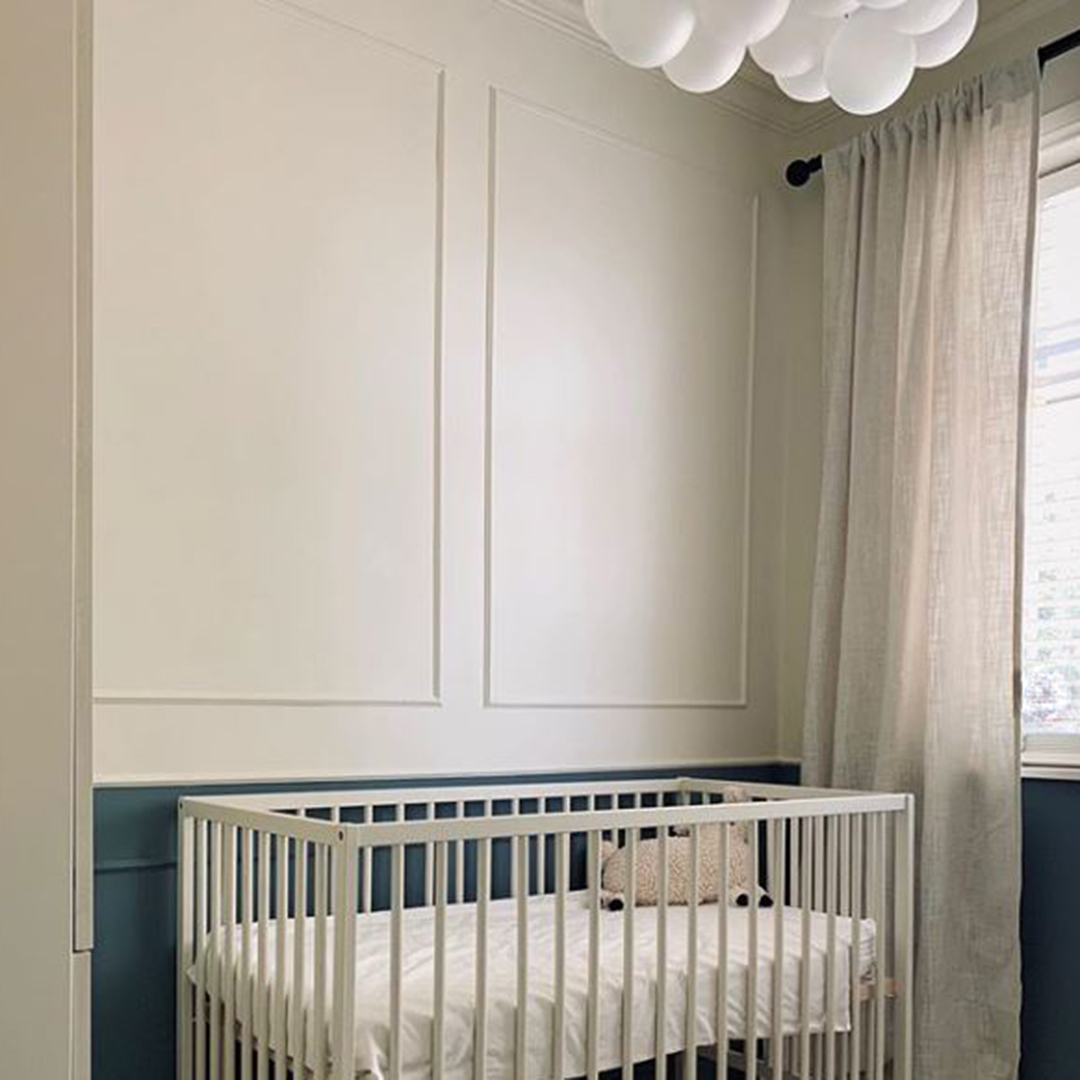 medium frosted bubble chandelier suspended above a cot in a white and navy nursery