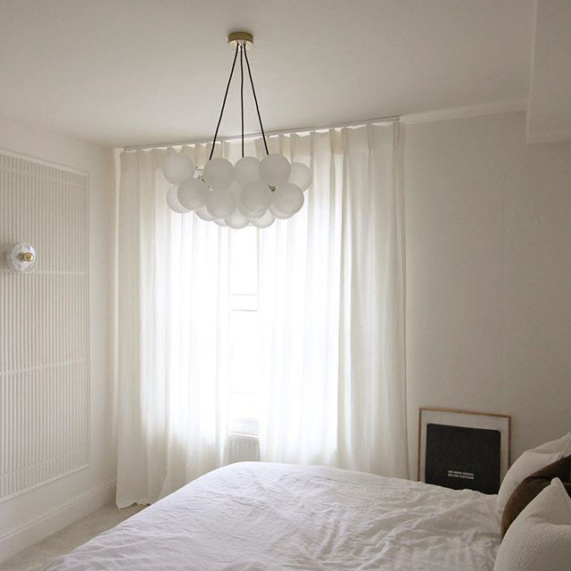 Frosted bubble chandelier suspended above a bed in an all white bedroom