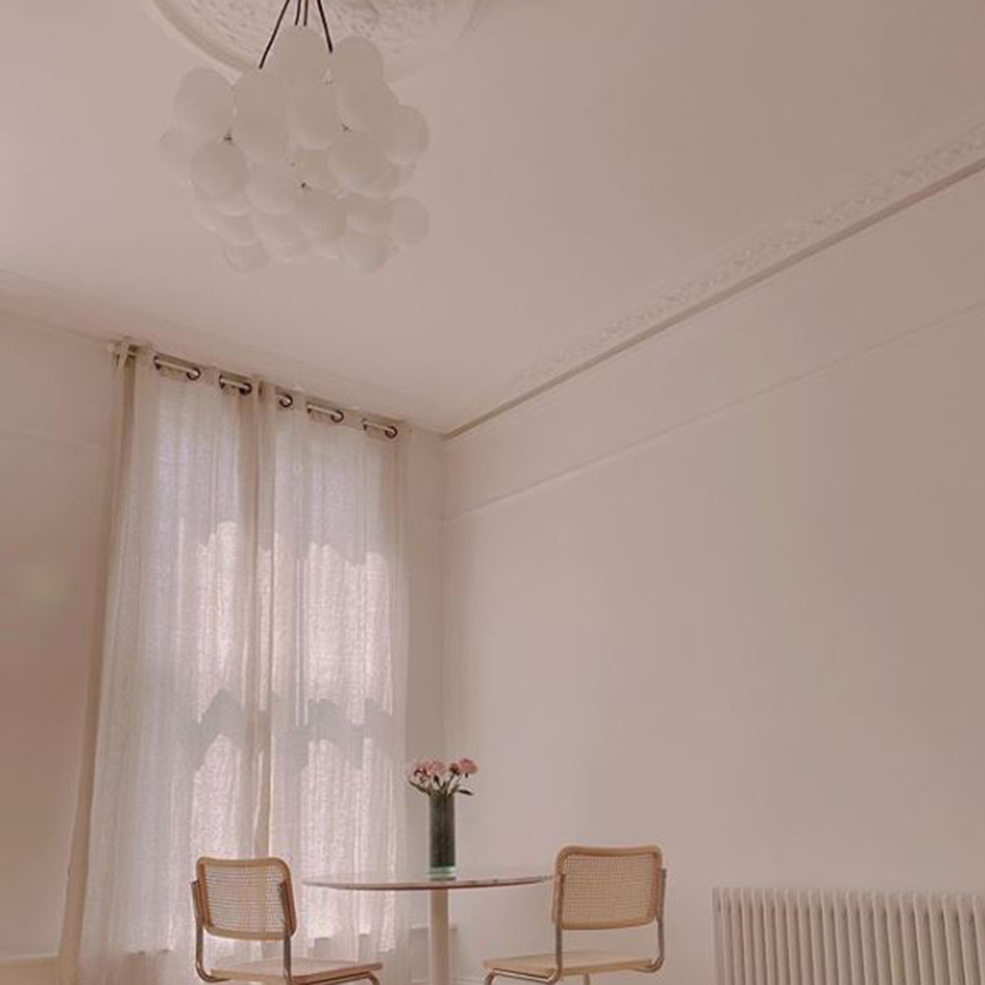 medium frosted bubble chandelier suspended above a dining table in a neutral interior