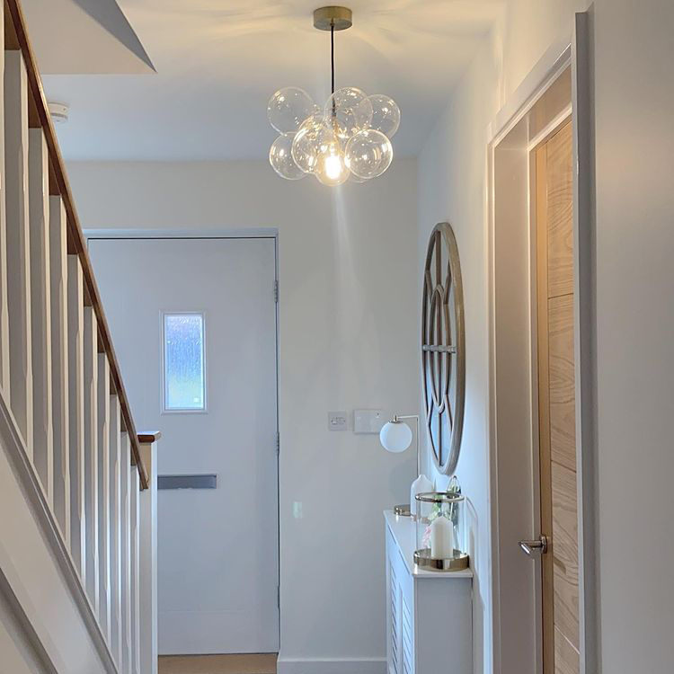 small bubble chandelier suspended in a white hallway