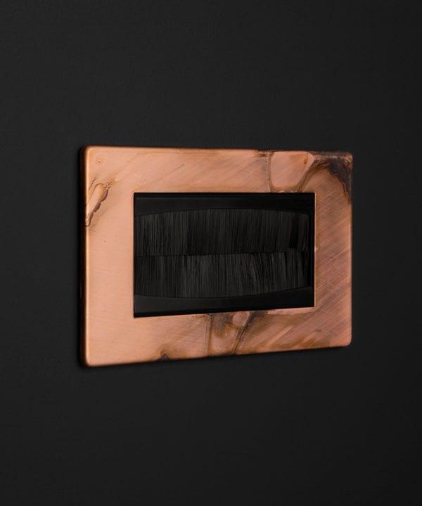 copper & black double brush plate against black background