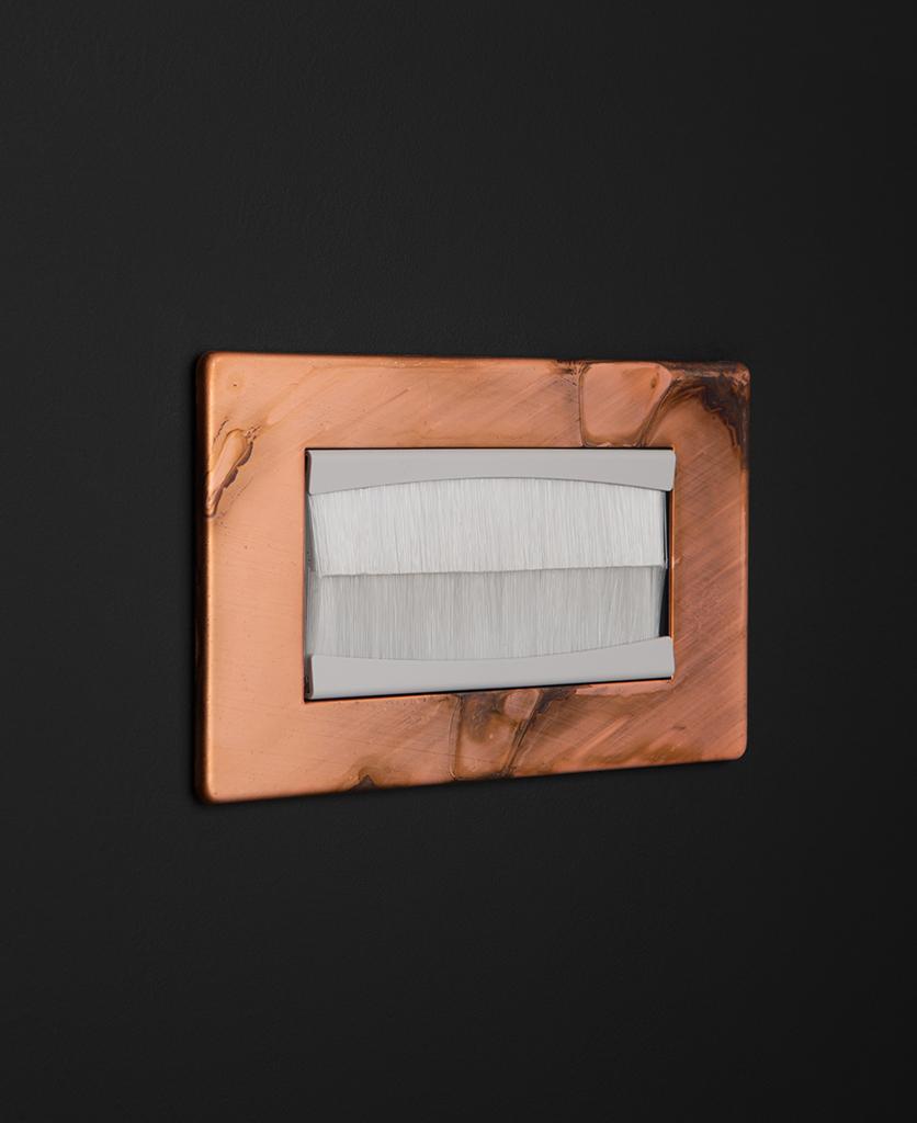 copper & white double brush plate against black background
