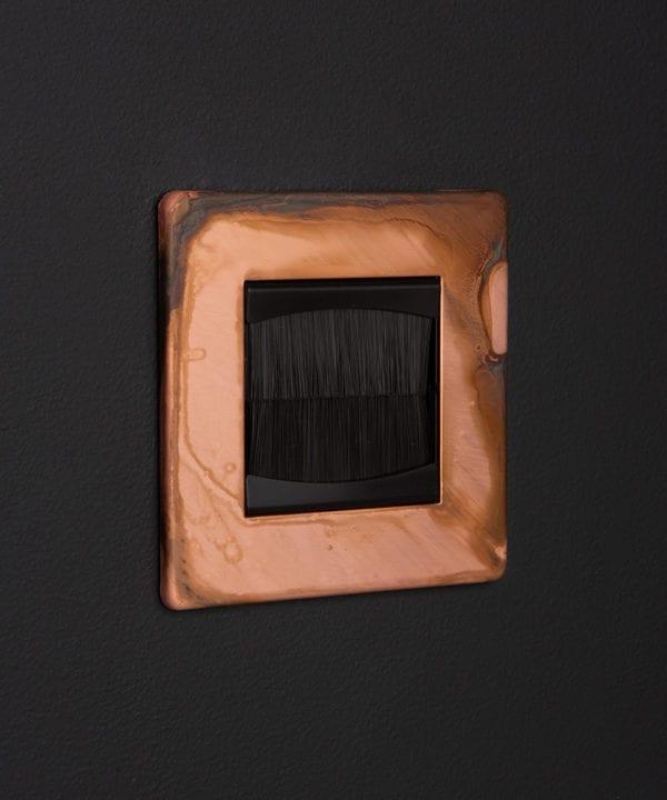 copper & black single brush plate against black wall