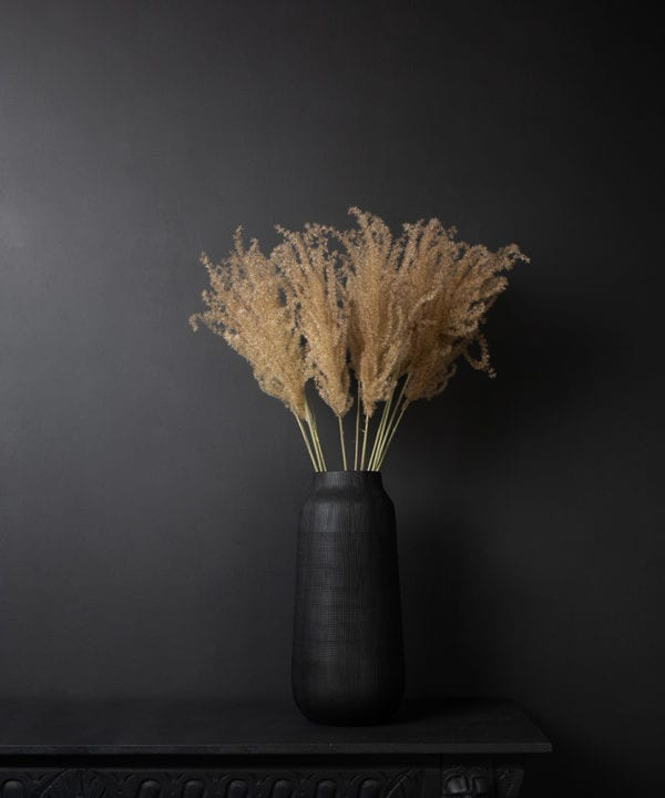 bouquet of fluffy reed grass in a black vase