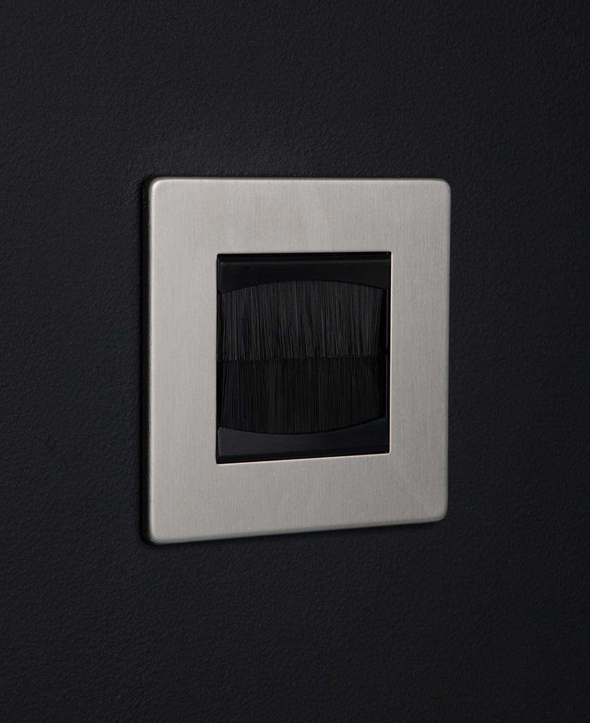 silver & black single brush plate against black background