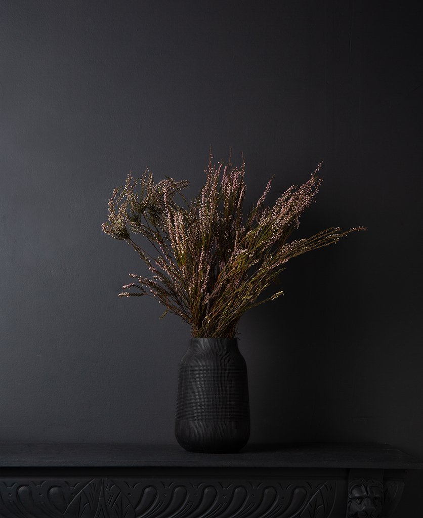 preserved heather bouquet in a black textured vase against a black background