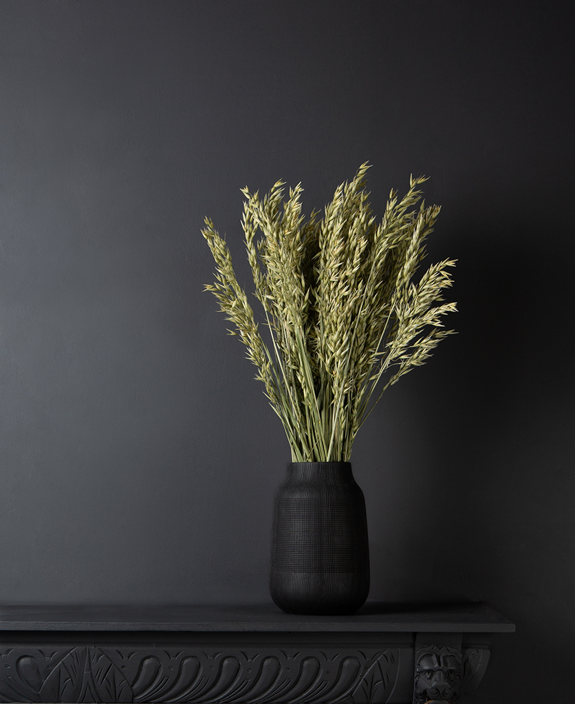 dried oat straw stems in a black textured vase against black background