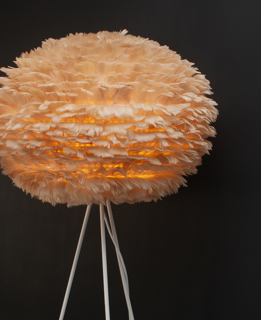 tripod floor lamp with brown feather ligth shade and white tripod base against black background