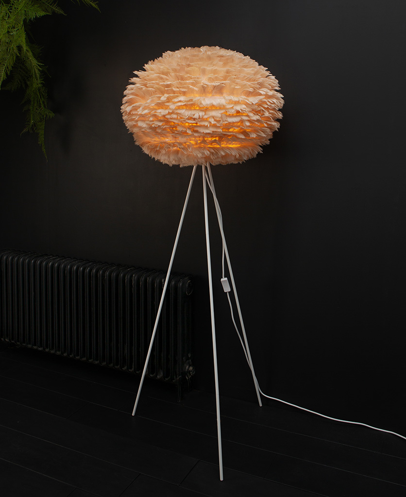 tripod floor lamp with brown feather light shade and white tripod base against black background