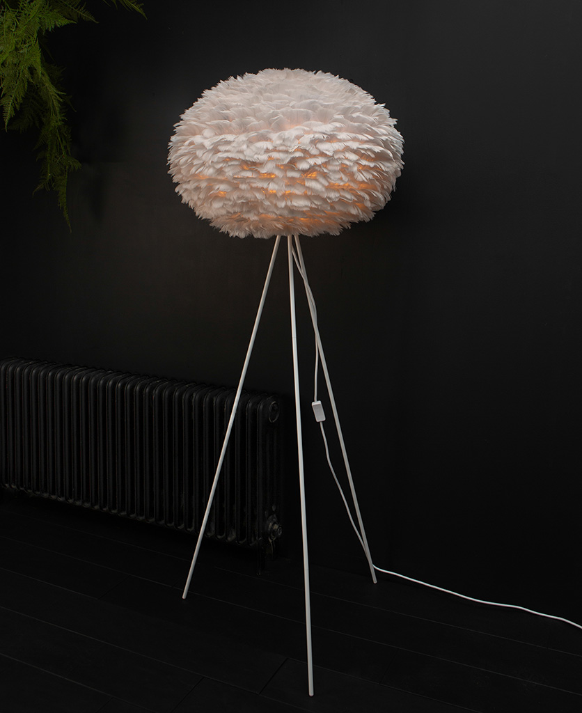 Grey tripod floor lamp with feather shade and white tripod base against black background