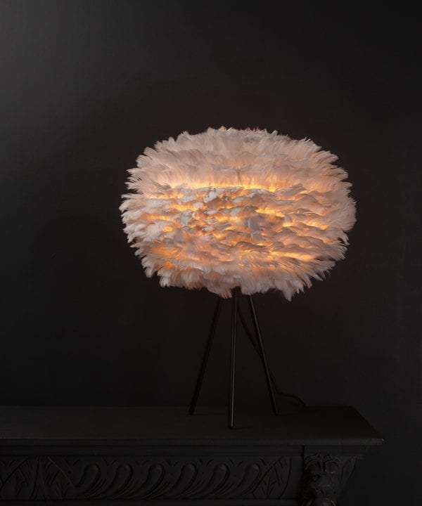 Umage grey table lamp with feather shade on black metal tripod base against black background