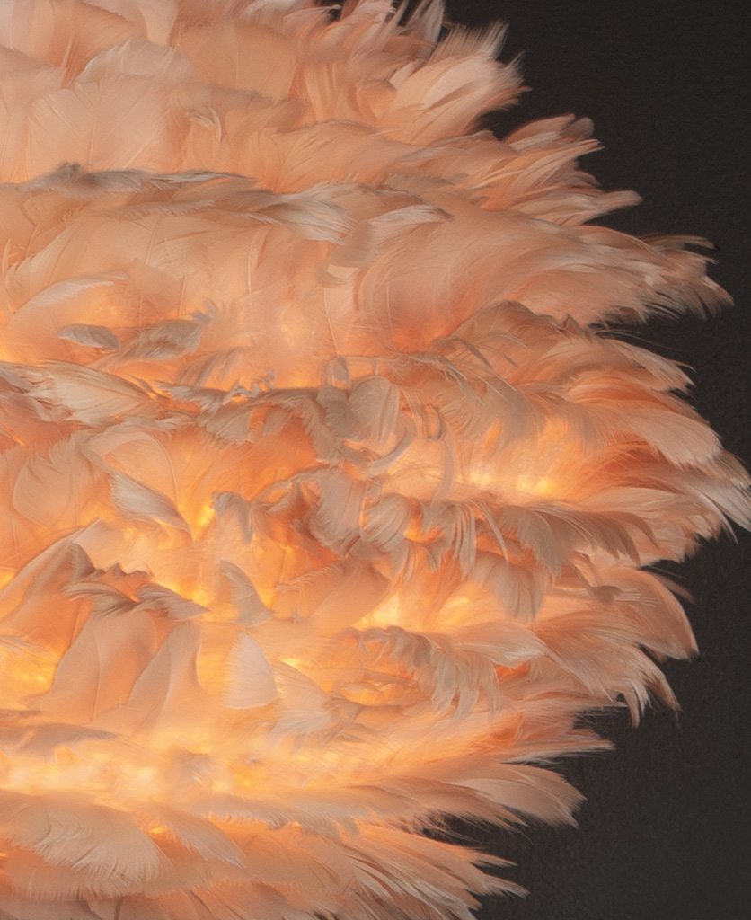 close up image of tripod table lamp with brown feather shade against black background