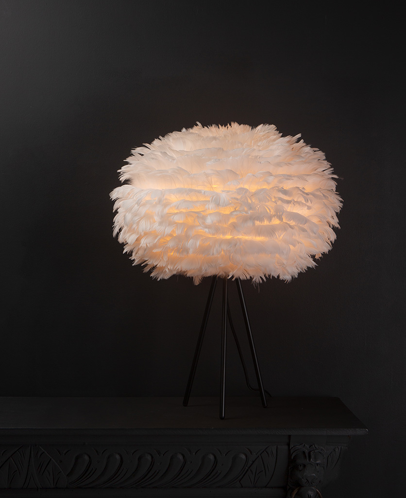 Umage white feather table lamp with feather shade on black metal tripod base against black background