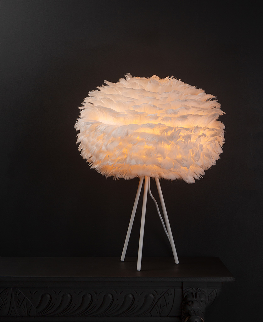 Umage white feather table lamp with feather shade on white metal tripod base against black background