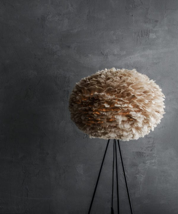tripod floor lamp with large brown feather lamp shade and black base against grey background