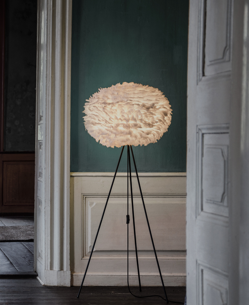 tripod floor lamp with large brown feather lamp shade and black base against lifestyle background