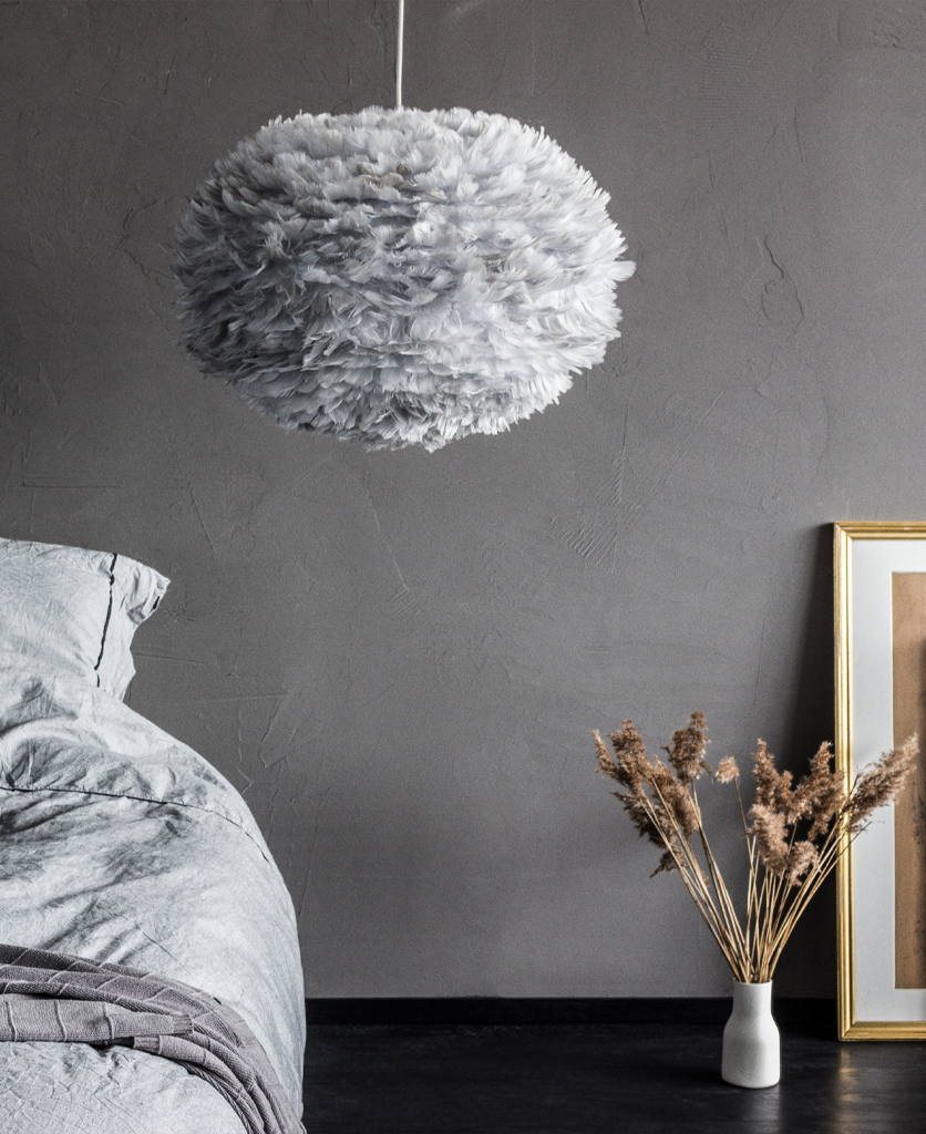 umage grey feather light suspended against grey wall besides a bed