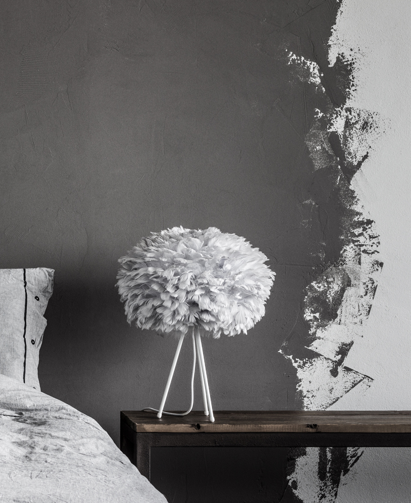 medium grey feather table lamp with white base against grey background