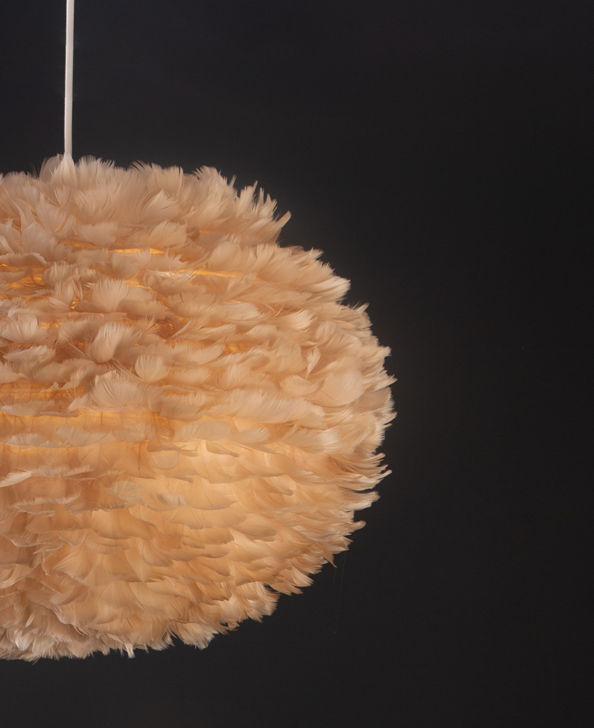 light brown umage feather pendant light with white cord set on black background