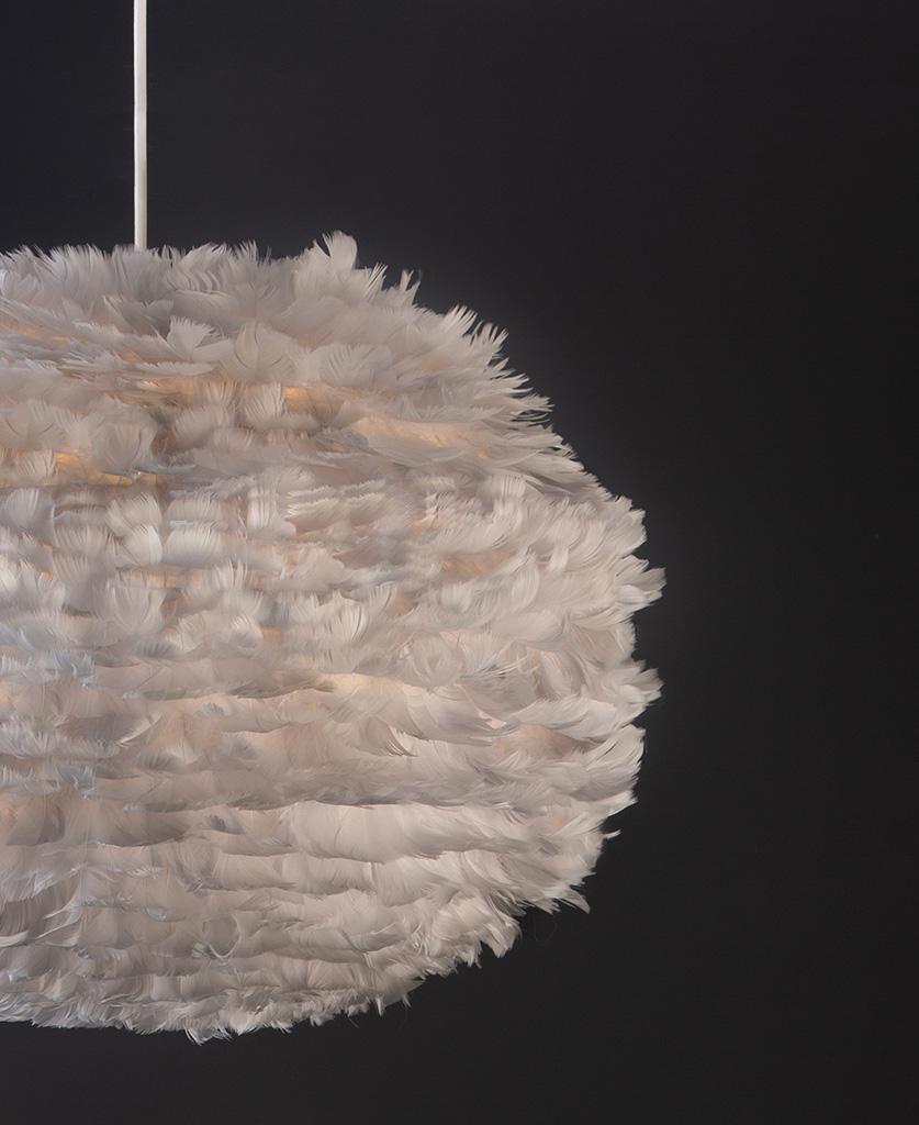 light grey umage feather pendant light with white cord set on black background close up