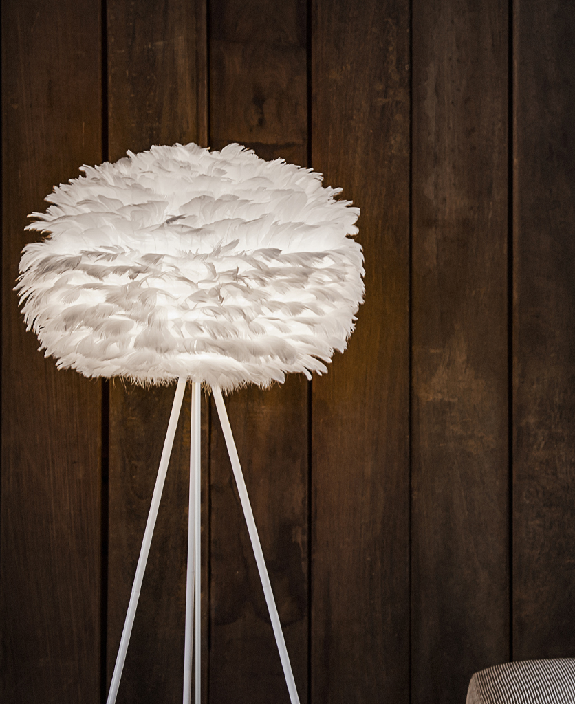 umage white feather floor lamp on white base lifestyle shot against wooden clad wall