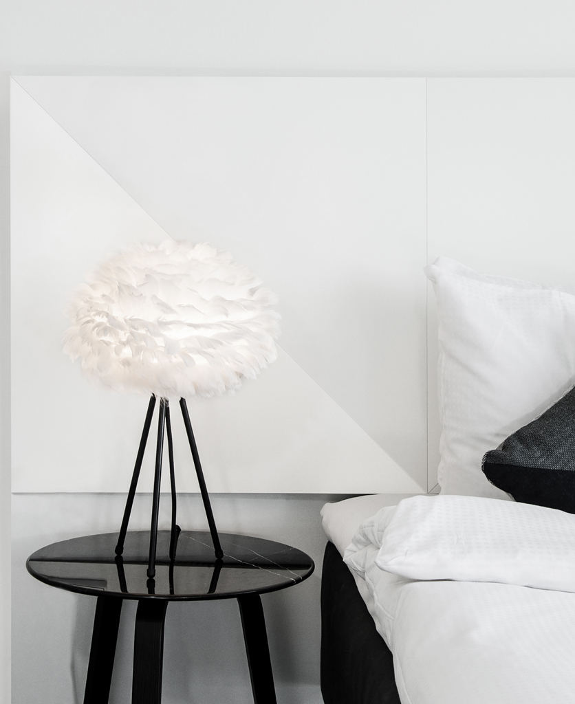 white feather table lamp with black base sat on a black table
