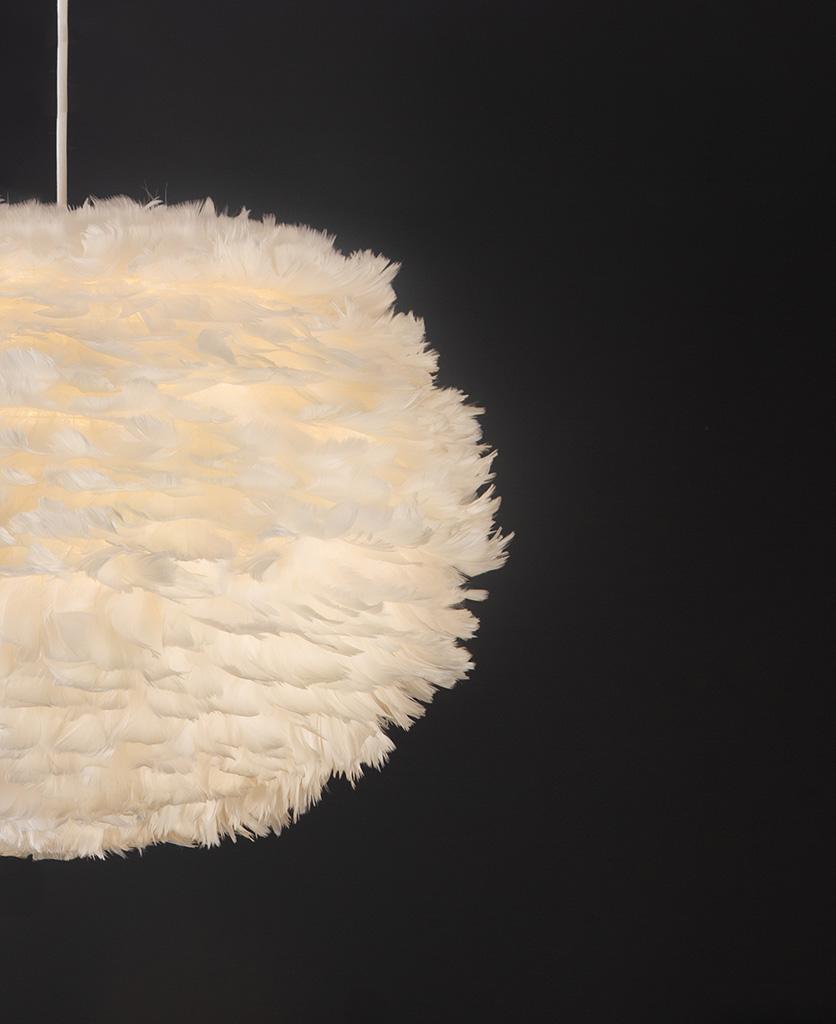 white umage feather pendant light with white cord set on black background close up