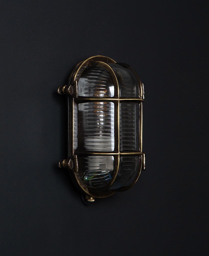 steve unlit aged brass bulkhead light with wingnuts against black background