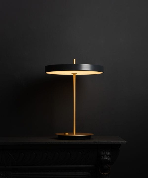 Umage asteria anthracite and brass table lamp with usb charging port on black background switched on