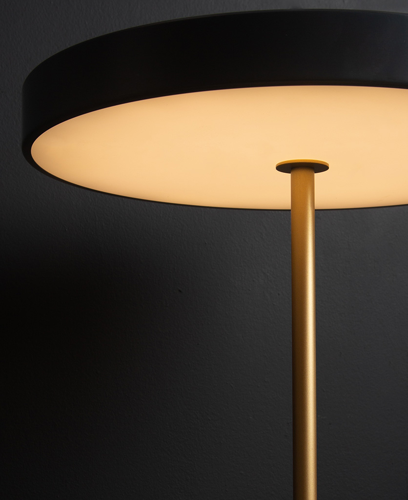 Close up of anthracite and gold umage asteria table lamp on black background switched on