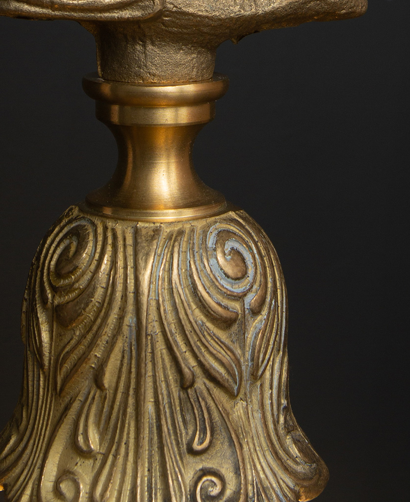 closeup of solid brass bulb holder with intricate pattern against black background
