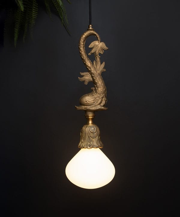 brass pendant fish light with lit bulb suspended from a length of black fabric cable against a black wall