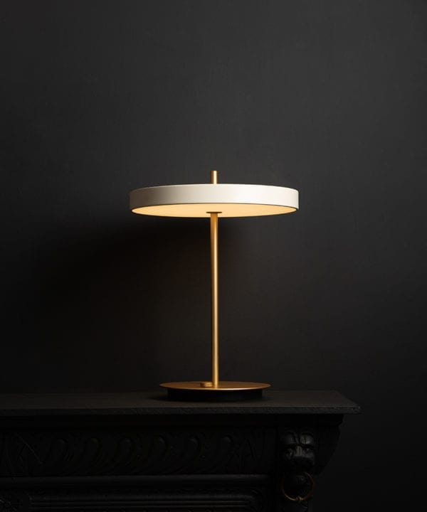 umage asteria pearl white and brass table lamp with usb charging port on black background switched on