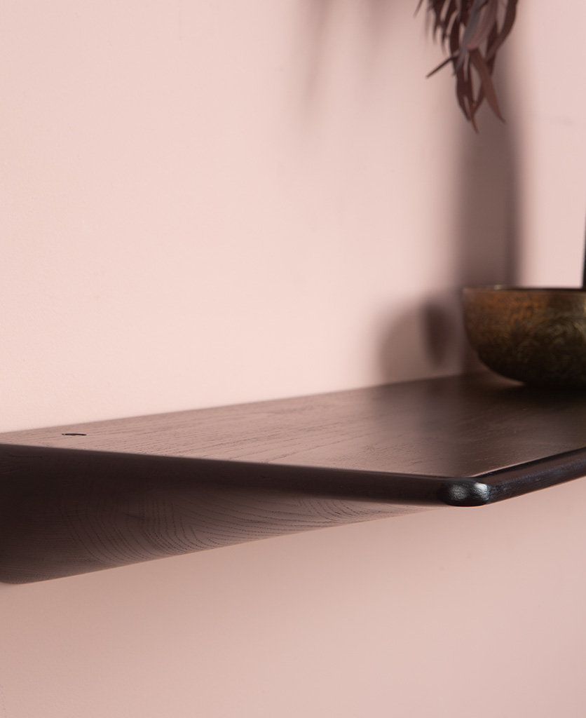 Close up of black floating shelf on a pink wall