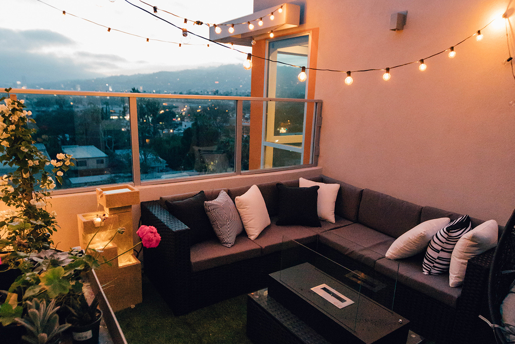 balcony at dusk with artificial grass, festoon lighting and rattan seating