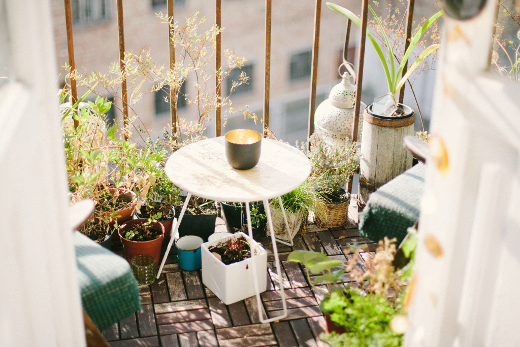 image of small balcony area with coffee table, parquet style floor and lots of plants