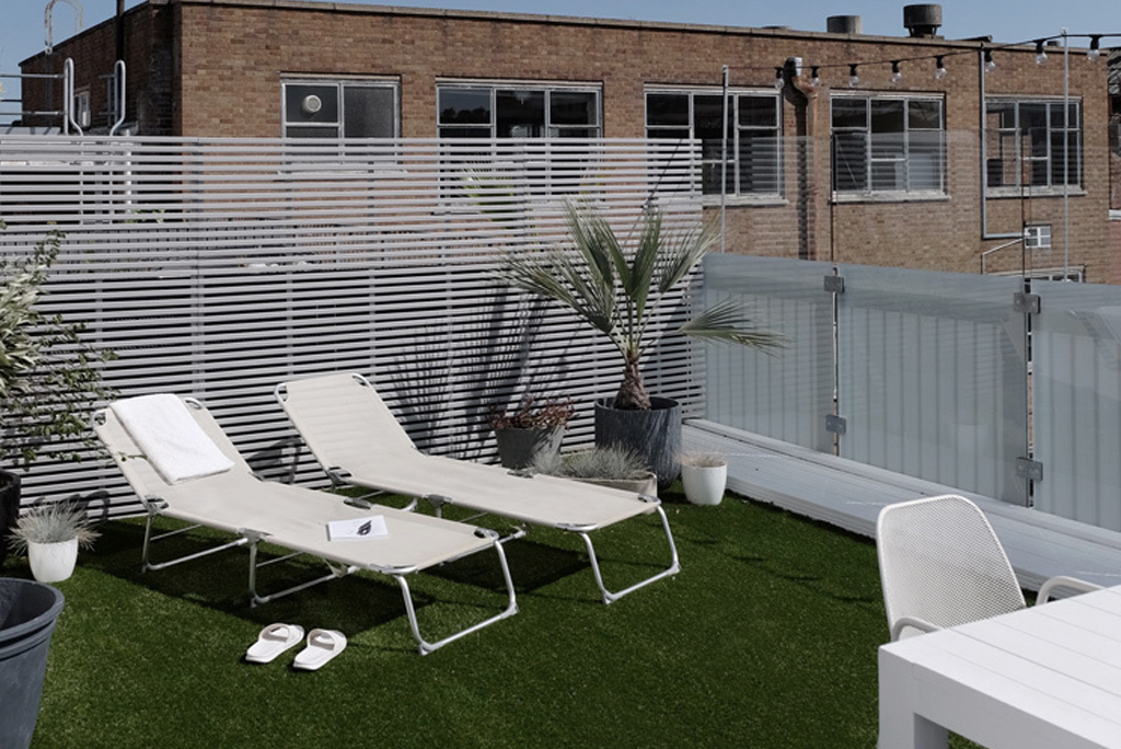 two white sun loungers on artificial grass on a white rooftop