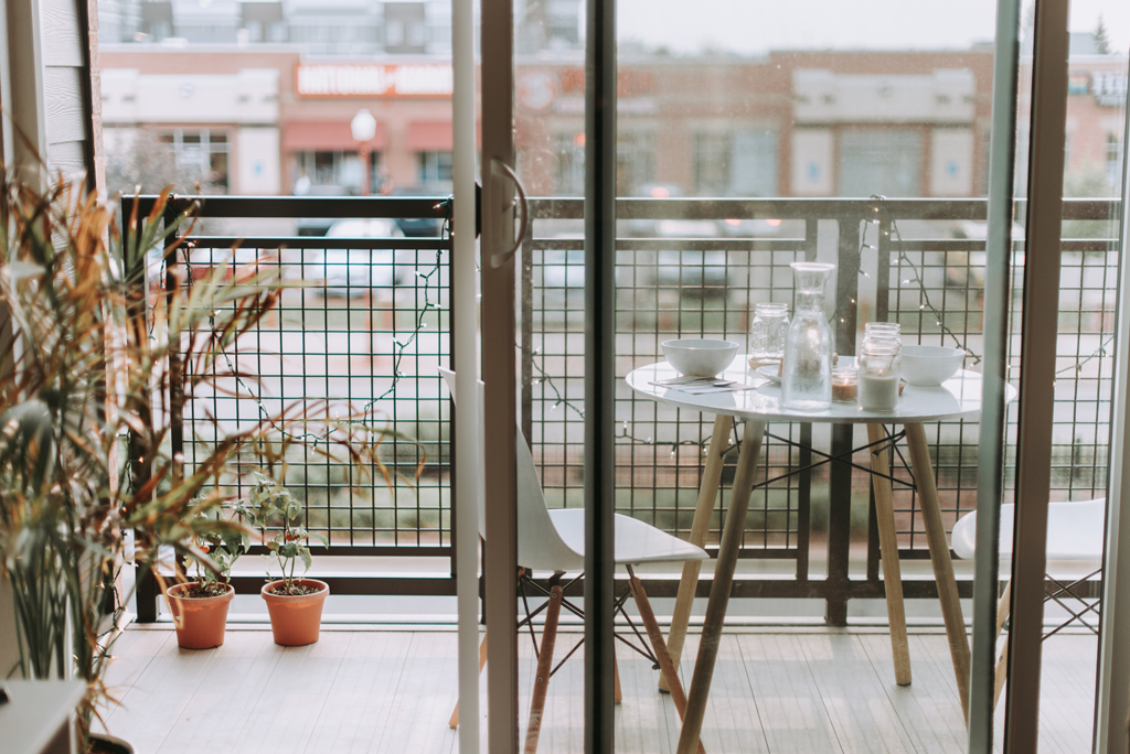 small balcony area with white bistro table