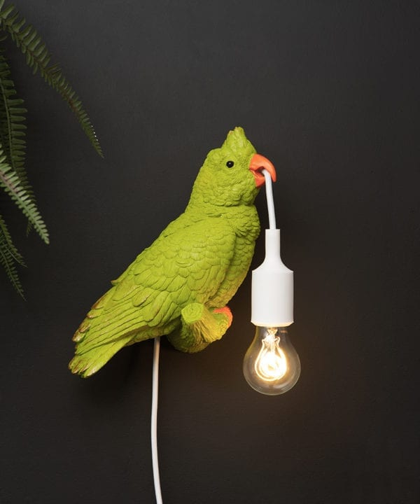 green parrot lamp holding a bulb in its beak attached to a black wall