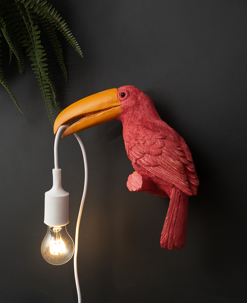 pink toucan bird light sat on a perch with a bulb in its beak on a black wall