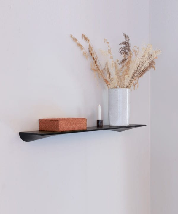umage flow black floating shelf with vase of flowers against a black wall