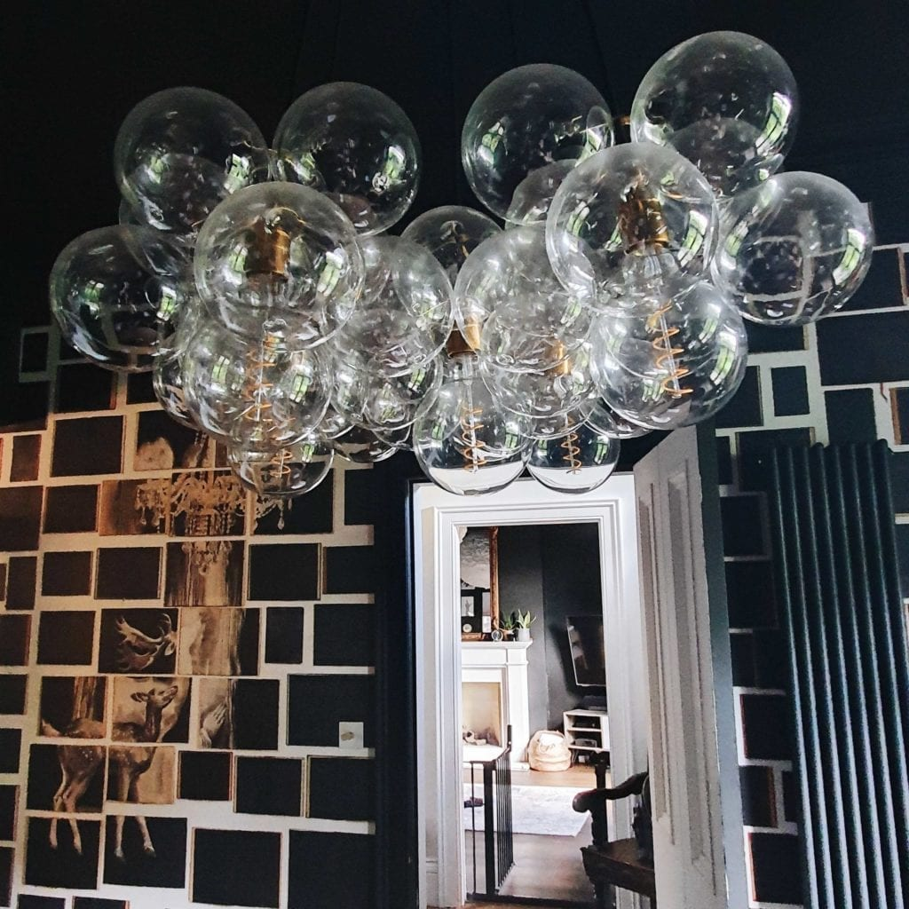 large clear bubble chandelier in black and white wallpapered living room