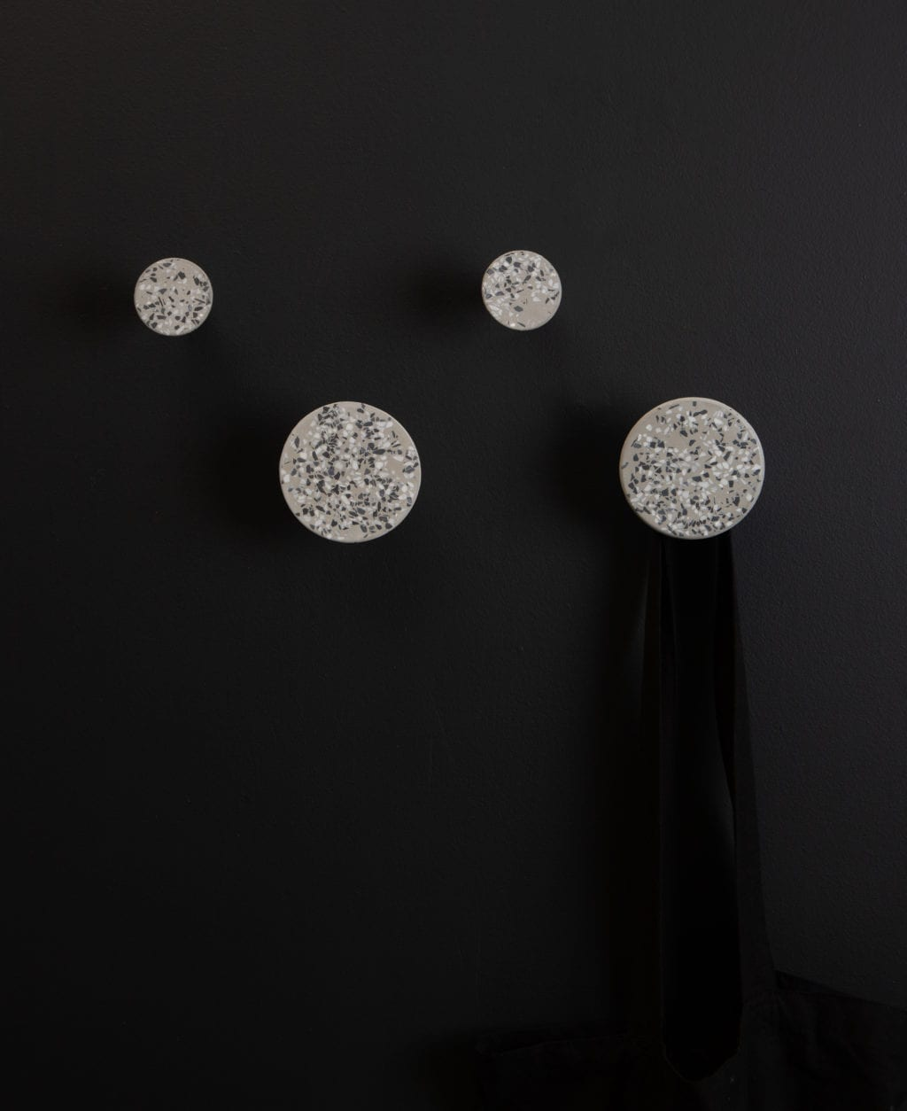 four grey terrazzo texture blomus wall hooks on a black wall