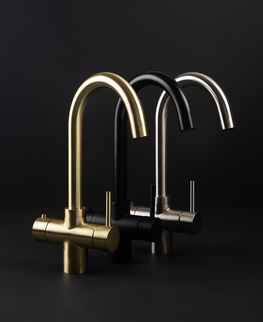 Black gold and silver hot water taps on a black background