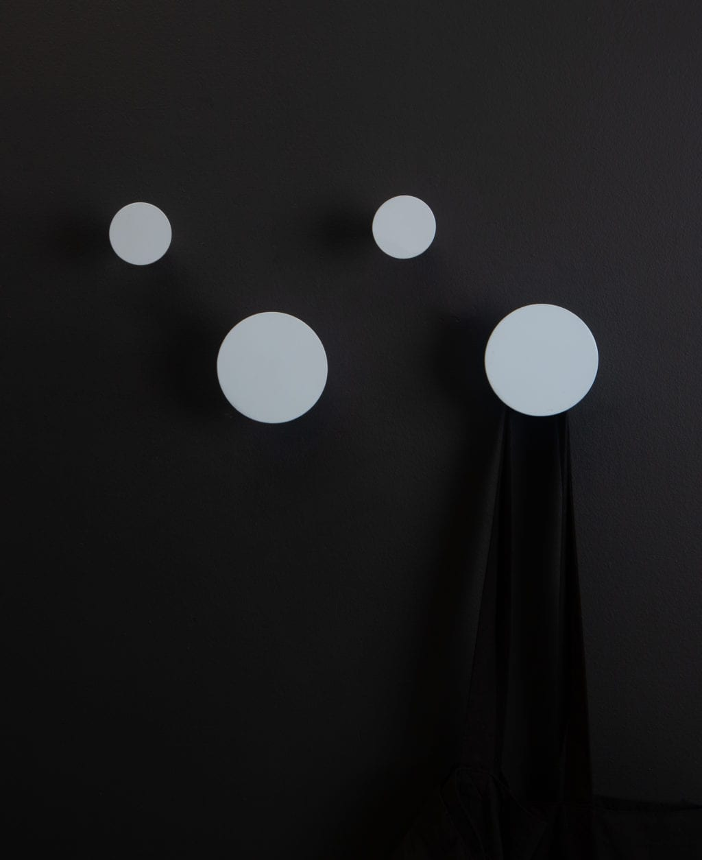 two large and two small light blue wall mounted coat hooks on a black wall