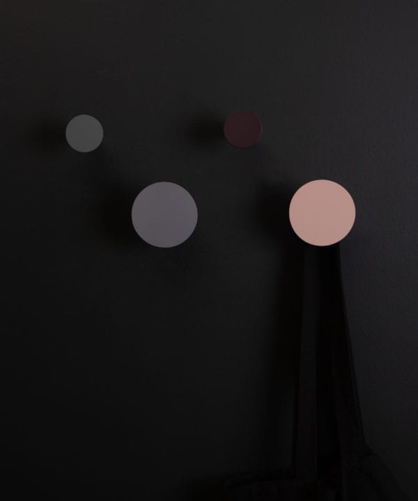 four multicoloured blomus wall mounted hooks on a black background